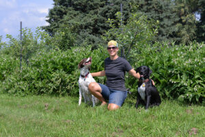 A Lakewinds Organic Field Fund Recipient Poses with Her Loyal Dogs